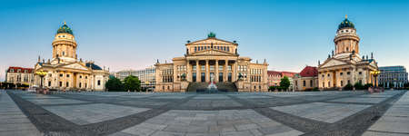 Panorama image of Gendarmenmarkt square in Berlin with French and German churches and Concert Hall at dawn