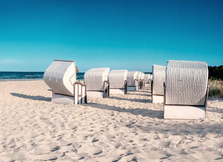 Sandy beach and traditional wooden beach chairs on island Rugen, Northern Germany, on the coast of Baltic Sea. Panorama, this image is toned. Stock Photo