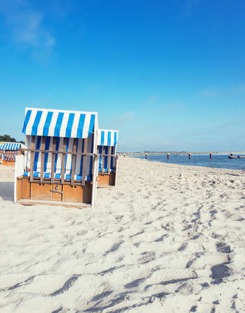 Sandy beach and traditional wooden beach chairs on island Rugen, Northern Germany, on the coast of Baltic Sea. Panorama, this image is toned. Editorial