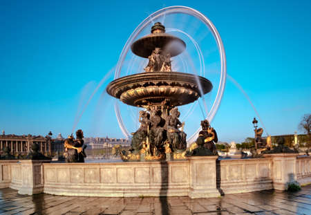 Fountain in the Place de la Concorde in Paris, France, with rotating ferris wheel in the background