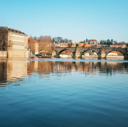 Prague, closeup on Charles bridge reflected in Vltava river in the morning, vertical panorama, space for your text. This image is toned.