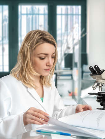 Young female scientist in the lab checks her laboratory journal Stock Photo
