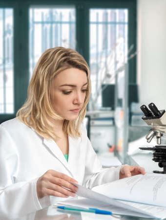 Biopsia: Young female scientist in the lab checks her laboratory journal Foto de archivo