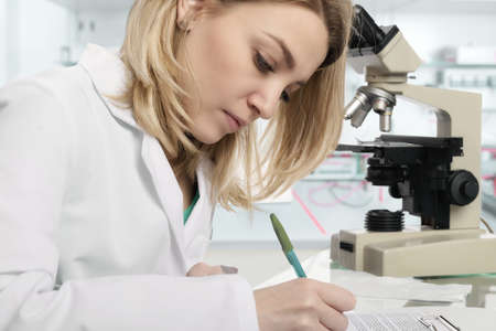 Young female scientist or tech writes report in modern laboratory, This image is toned.