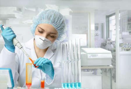 El técnico o científico joven carga la muestra líquida en el tubo de ensayo con una pipeta de plástico. Someras DOF, se centran en los ojos y las manos.