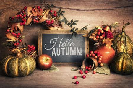 """Tafel mit Chakboard Text """"Hallo Herbst"""" mit Herbst Dekorationen auf Holz. Dieses Bild ist getönt."""