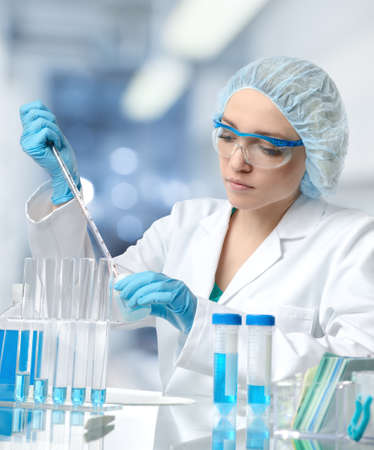 Young female tech or scientist loads liquid sample into test tube with plastic pipette. Shallow DOF, focus on the face Stock Photo