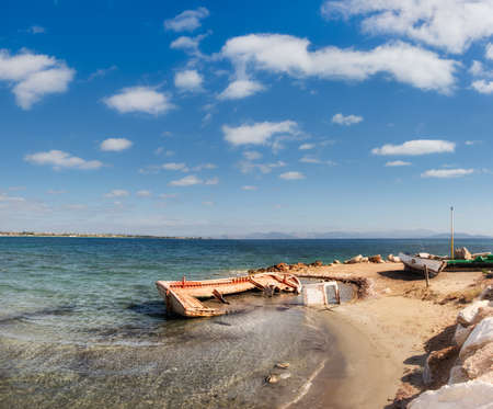 Old fisherman boats on the shore of Aegean sea in Greece Stock Photo