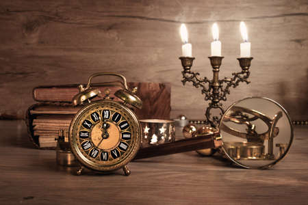 europeans: Vintage alarm clock showing five to twelve on the wooden table in study room. Space for your greeting. Happy New Year 2017! This image is toned.