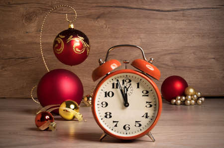 Vintage alarm clock showing five to twelve on the wooden table with Christmas decorations. Text space. This image is toned. Stock Photo
