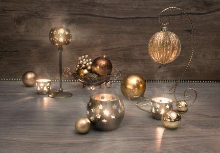 traditonal: Vintage Christmas decorations, baubles and burning candles on wood. This image is toned.