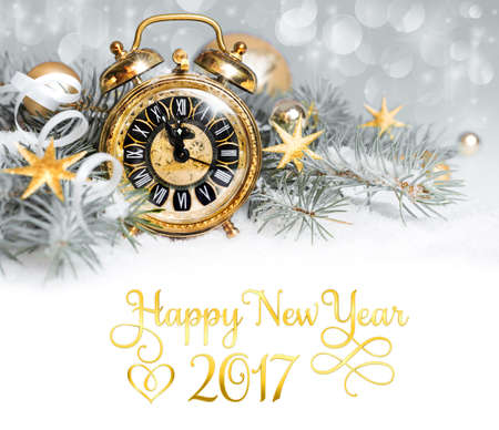 12 month old: Alarm clock and decorations on snow. New Year greeting card, caption Happy New Year 2017 in English on white background, can be replaced with your greeting text. Stock Photo