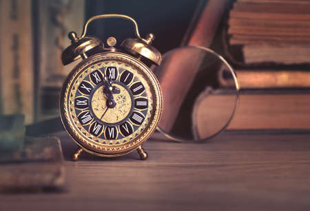 room for your text: Happy New Year 2017! Vintage alarm clock showing five to twelve among old books in study room. Space for your greeting text. This image is toned.