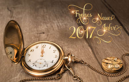 Vintage watch on a wooden background showing five to twelve. New Year greeting card, caption Frohes Neues Jahr 2017 in German. This image is toned.