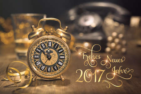 twelve month old: Vintage alarm clock showing five to midnight and an old phone. New Year greeting card, caption Frohes Neues Jahr 2017 in German. This image is toned.