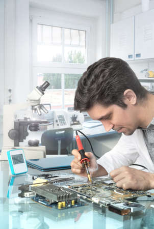 technical service: Young energetic male tech or engineer repairs electronic equipment, focus on the solrer tip and eyes