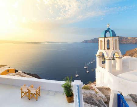 thera: Church in Oia with traditional cycladic belfry, Santorini, Greece. Panoramic image.