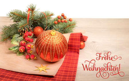 Wooden background with decorated Christmas tree twigs, text on the picture means Merry Christmas in German