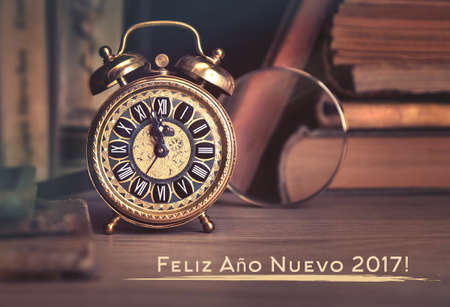Happy New Year 2017! Vintage alarm clock showing five to twelve among old books in study room. Greeting text means Happy New Year 2017 in Spanish
