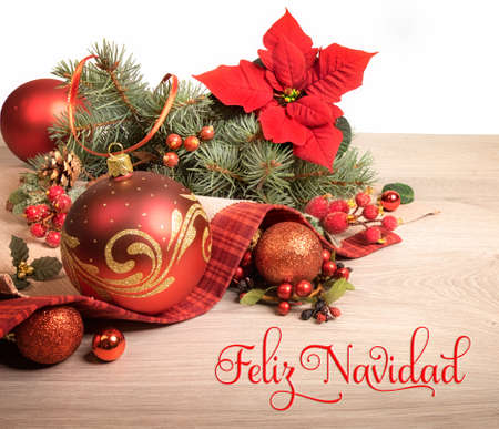 Wooden background with poinsettia and decorated Christmas tree twigs, text on the picture means Merry Christmas in Spanish.