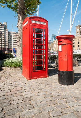 colorize: LONDON, UK- APRIL 16, 2014: Phone booth and a post box at St Katharine Docks, a quiet place with boats and old houses East from the Tower of London Editorial