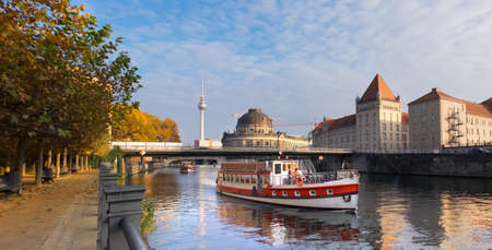Berlin, Spree river in Autumn with Bode museum and Alexanderplatz TV tower and touristic boat on the foreground