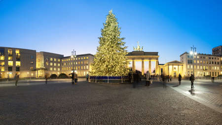 quadriga: BERLIN, GERMANY - DECEMBER 21, 2016: Panorama of Branderburger Gate in evening illumination with Christmas tree in front. Life in the capital is going back to normal two days after the terror attack on the Christmas market.