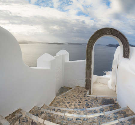 Romantic Santorini island in Greece: staircase through the arch leading to magestic view over caldera, panoramic image.