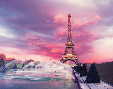 romance sky: Eiffel tower on a sunset half-lit with last rays of the setting Sun. Panoramic toned image.