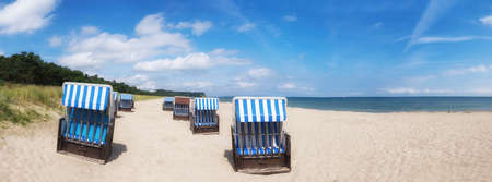 Sandy beach and traditional wooden beach chairs on island Rugen, Northern Germany, on the coast of Baltic Sea Stock Photo