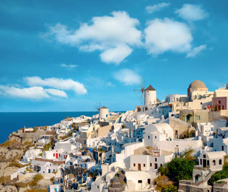 Beautiful Santorini in Greece - traditional windmill and apartments in Oia village on a sunny day. Panoramic image. This picture is toned.