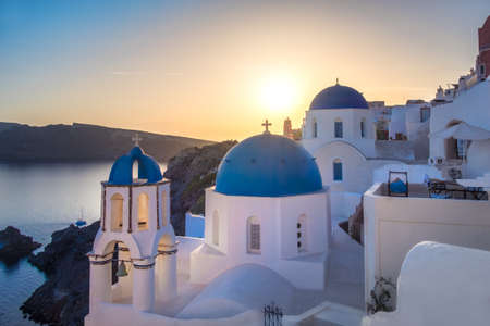 Sunset over local church with blue cupola in Oia village, Santorini island, Greece. Panoramic image.