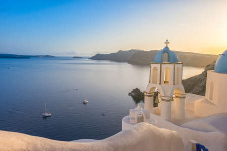 Sunset over local church with blue cupola in Oia village, Santorini island, Greece Stock Photo