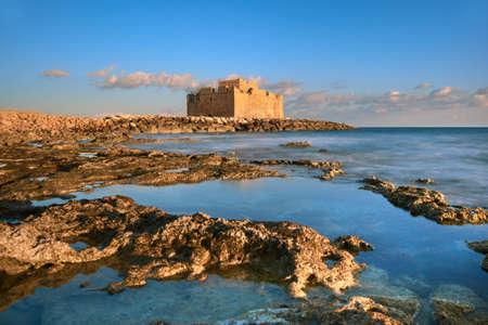 """Het Kasteel van de Haven van Pafos, dat ook als """"Turks Kasteel"""" in Pathos, Cyprus op een zonsondergang wordt bekend"""