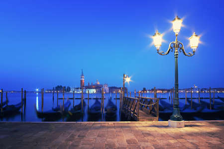 Embankment of Grand Canal at night, lamp post with goldolas and San Giorgio di Maggiore behind. The shot is taken in Vence, Venezia, Italy. Tilt-shift lens,  both lamp and the church are in focus.