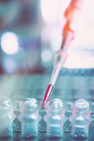 pcr: Scientific background with tools for DNA amplification and sequencing. Shallow DOF, most of the image is blurred. This image is toned. Space for your text. Stock Photo