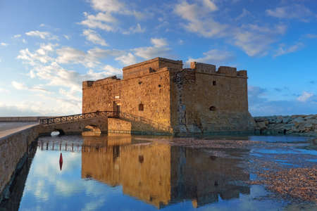 Pafos Harbour Castle, also known as Turkish Castle in Pathos, Cyprus, on a sunset with reflection Фото со стока