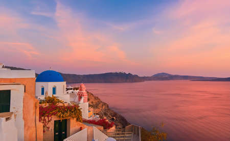 Oia village, Santorini island, Greece on a sunrise with local curch overlooking famous volcanic caldera. Panoramic toned image.