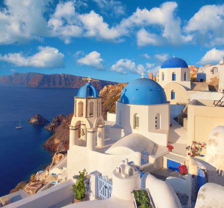 ギリシャ サントリーニ島イア村で青のキューポラと地元の教会。パノラマ画像。