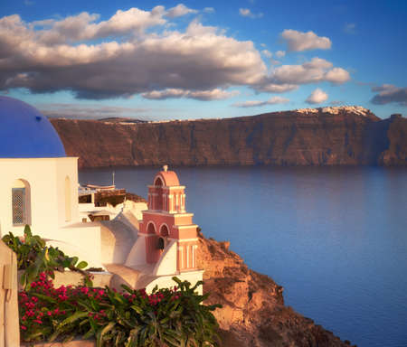 Oia village, Santorini island, Greece on a sunset with local curch overlooking famous volcanic caldera. Panoramic toned image.