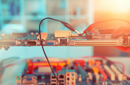 Closeup on electronic board in hardware repair shop, blurred and toned image, electronics background Stock Photo