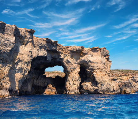 water  panoramic: Limestone rock caves and blue Mediterranean water of Comino island, Malta. Panoramic image