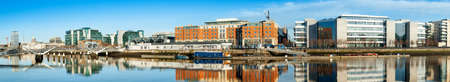 Dublin, Ireland, panoramic view over Liffey river with modern buildings and Sean OCasey bridge in the back.