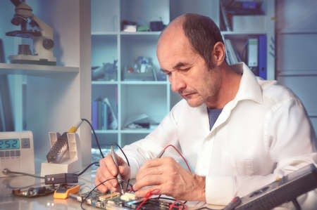 Senior male tech tests electronic equipment, toned image photo