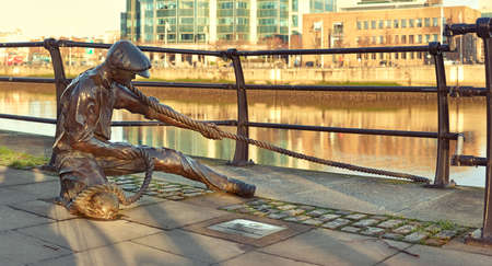 liffey: The Linesman statue at Liffey river in Dublin, Ireland. Toned panoramic image