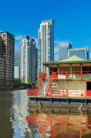 LONDON, ENGLAND - MAY 3, 2013: Canary Wharf skyline and South Dock, London, England. Red building at front is Lotus, Chinese restaurant. Editorial