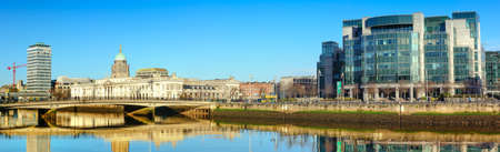 DUBLIN, IRELAND - 4 FEBRUARY 2017: Panoramic image of river Liffey waterfront in Dublun, on the right is IFSC Custom House Quays, on the right historic Customs house,
