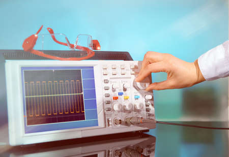 Modern electronic oscilloscope on abstract background, hand tuning a dial. This image is toned