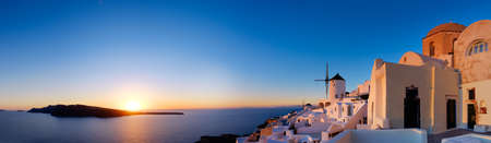 Sunset over Santorini island in Greece. Traditional church, apartments and windmills in Oia village on a sunset, panoramic image.