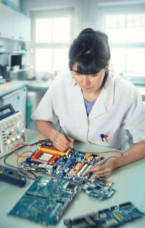 technical service: Young female tech or engineer repairs electronic equipment in research facility. Shallow DOF, focus on the eyelashes. This image is toned.